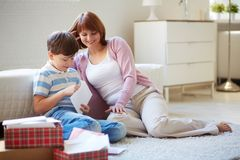 Opening letters. Portrait of cute boy opening envelope with his mother near by at home Royalty Free Stock Photography