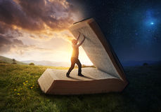 Opening the light of the Bible. A man opens up the pages of the Bible stock photography