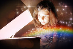 Opening the magic chest. A little girl opening a magic chest and setting the rainbow free amongst glittering stars. Christmas or birthday concept – the magic Royalty Free Stock Images