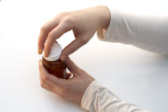 Opening a medicine bottle. White background royalty free stock images
