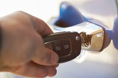 Opening modern car door. With classic key close-up stock photography