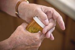 Opening Prescription Medicine. Older woman's hand opening a bottle of prescription medicine Royalty Free Stock Photos