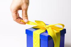 Opening present - with clipping path. Suprise present in a nice blue package with yellow bow Royalty Free Stock Photography