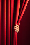Opening the red curtain. Male hand disclose the scene shifting the red curtain Royalty Free Stock Images