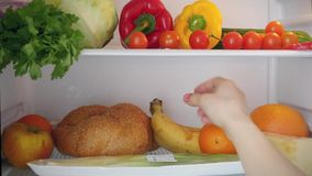 Opening the refrigerator door, a female hand puts stock footage