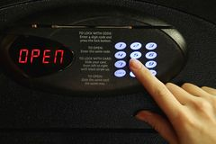 Opening of safe. Closeup of a female hand using the code keypad on a metal safe to open it Royalty Free Stock Photography