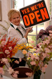 Opening shop. A florist putting the open sign in the shop window royalty free stock photo