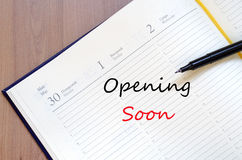 Opening Soon Concept. Yellow blank notepad on office wooden table Opening Soon Concept Stock Images