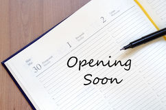 Opening soon concept. Yellow blank notepad on office wooden table Opening soon concept Royalty Free Stock Images