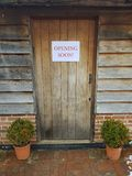 Opening soon sign on wood door. Opening soon sign attached to an outdoor closed wooden door Royalty Free Stock Photo