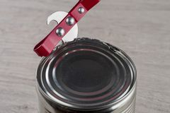 Opening a tin can with a can opener. On a neutral background royalty free stock photos