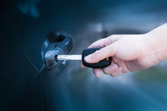 Opening unlocking door with car key. Car keys closeup of hand holding key to lock or unlock doors Stock Photography