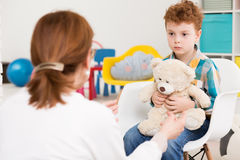 Opening up for new emotions. Red-haired, autistic boy with teddy bear concentrated on his therapist Stock Photography