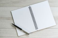 Opening white blank note paper and pen on the left with on light. Grey wooden table background with copy space royalty free stock photography