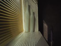 The opening of the window with two vases, closed with golden blinds, slanting shadows from slots, creating radical shadows, the ri. The opening of the window Stock Photo
