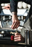 Opening a wine bottle with corkscrew in a bar Stock Image