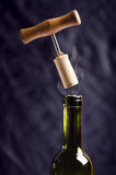 Opening a wine bottle with a corkscrew on a black background. Wine bottle with steam. Levitation of corkscrew. Isolated. Stock Photo