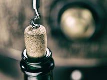 Opening wine bottle. Oak wine keg at the background. Stock Images