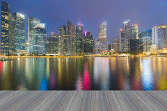 Opening wooden floor, Marina bay business office during twilight with water reflection Stock Image