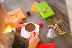 Openings aanwezige Kerstmis Vrouwen` s handen die een kop van hete koffie op rustieke houten lijst houden Royalty-vrije Stock Afbeelding