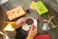 Openings aanwezige Kerstmis Vrouwen` s handen die een kop van hete koffie op rustieke houten lijst houden Stock Afbeelding