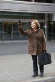 Openlucht bedrijfsvrouw die een taxicabine begroet Royalty-vrije Stock Afbeeldingen