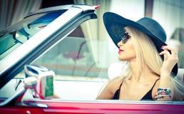Openlucht de zomerportret van modieus blonde uitstekende vrouw die een convertibele rode retro auto drijven Modieus aantrekkelijk Royalty-vrije Stock Foto's