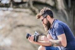 Openlucht fotografisch materiaal Hipstermens in zonnebril brutale fotograaf met camera Rijpe hipster met baard royalty-vrije stock foto