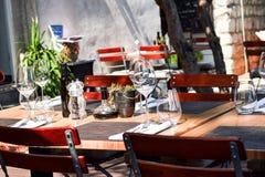 In openlucht geplaatste dinerlijst, Houten lijst en stoelen, steenachtergrond Royalty-vrije Stock Afbeeldingen