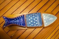 Openlucht het eten - Drie stuk blauwe dienende schotel in de vorm van een vissenzitting van een rode terraslijst - hoogste mening royalty-vrije stock foto