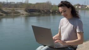 In openlucht het werken met laptop Meisje met laptop door de rivier Een de lente zonnige dag stock footage