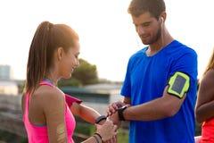 Openlucht jong paar dat zij smartwatch na het lopen gebruikt Stock Foto