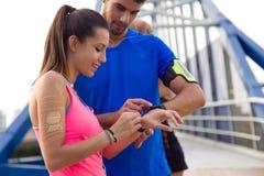 Openlucht jong paar dat zij smartwatch na het lopen gebruikt Royalty-vrije Stock Afbeeldingen