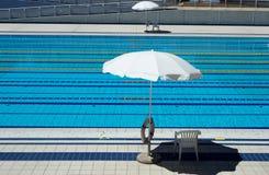Openlucht Olympisch zwembad met stegen voor rassen en 2 paraplu's per kant voor de badmeesters royalty-vrije stock fotografie