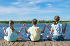 In openlucht, op de pijler, dichtbij het water, zijn de kinderen bezig geweest met ontspanning in de vorm van yoga stock afbeeldingen