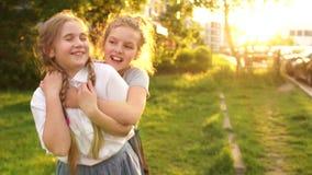 Openlucht Portret De tienermeisjes koesteren en lachen op een achtergrond van zonlicht, gelukkige kinderjaren, schoolvakantie stock videobeelden