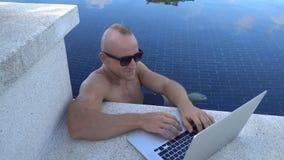 In openlucht portret van de knappe gelukkige mens in zonnebril die aan laptop computer in een dak zwembad werken stock footage
