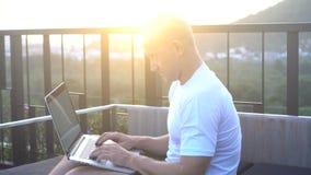 In openlucht portret van de knappe jonge mens die aan een laptop computer werken terwijl het zitten op een dak over mooie zonsopg stock video
