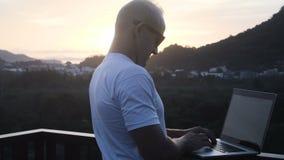 In openlucht portret van de knappe jonge mens die aan een laptop computer werken terwijl status op een dak over mooie zonsopgang stock footage