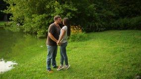 In openlucht portret van het mooie paar die bij het stadspark kussen Vrouw en man in liefde buiten stock video