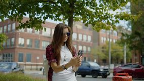 In openlucht portret van jong leuk meisje die in modieuze uitrusting en gemerkte glazen een selfie maken stock video