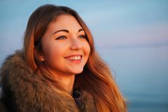 In openlucht portret van jong mooi glimlachend meisje met rode wangen in de winter dichtbij het bevroren meer stock afbeeldingen