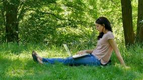 In openlucht Portret van Jonge Donkerbruine Vrouw met Witte Laptop Zitting op Groen Gras in het Park en het Werken met Genoegen stock videobeelden