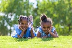 Openlucht portret van leuke jonge zwarte zusters die op Th liggen Royalty-vrije Stock Foto's