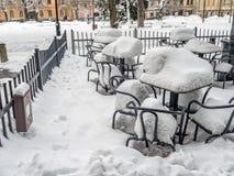 In openlucht restaurantstoelen en lijsten met dikke sneeuwdekking die worden behandeld Royalty-vrije Stock Fotografie
