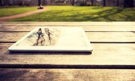In openlucht rustieke houten lijst met digitale tablet, die op bomen, met exemplaarruimte wijzen Stock Afbeelding