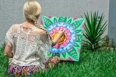 In openlucht schilderend, trekt een jong vrouwenblonde een mandala op de aardzitting in het gras royalty-vrije illustratie