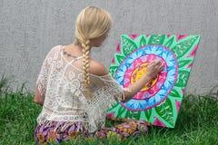 In openlucht schilderend, trekt een jong vrouwenblonde een mandala op de aardzitting in het gras royalty-vrije stock foto's