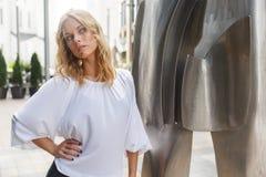 In openlucht verbazend blonde vrouw met krullend haar nabijgelegen modern beeldhouwwerk Royalty-vrije Stock Fotografie