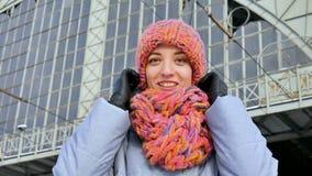 In openlucht vrouwelijk portret van leuk volwassen meisje die heldere kleurrijke hoed met sjaal dragen en de camera bekijken stock footage
